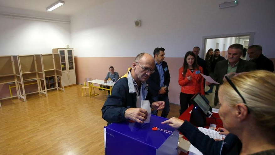 A man casts his ballot at a polling station in Podgorica, Montenegro, Sunday, Oct. 16, 2016. The vote pits Prime Minister Milo Djukanovic's long-ruling Democratic Party of Socialists against a cluster of pro-Russian and pro-Serbian opposition groups that staunchly oppose the country's NATO bid. (AP Photo/Darko Vojinovic)
