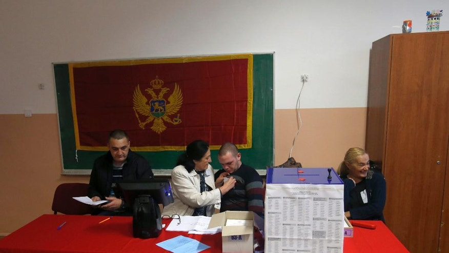 Election commission's representatives prepare for voting at a polling station in Podgorica, Montenegro, Sunday, Oct. 16, 2016. The vote pits Prime Minister Milo Djukanovic's long-ruling Democratic Party of Socialists against a cluster of pro-Russian and pro-Serbian opposition groups that staunchly oppose the country's NATO bid. (AP Photo/Darko Vojinovic)