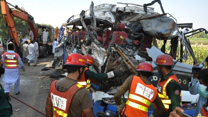 A Pakistani rescue team work on the wreckage of a deadly accident involving two buses, in Khanpur, Monday, Oct. 17, 2016. Pakistani officials say the death toll from a head-on collision of two passenger buses in central Pakistan is over two dozen. They say tens of people were injured in the crash, many of whom remain in critical condition. Police say speeding seems to have been the cause of the accident, which occurred on a dangerous curve in Rahim Yar Khan district. (AP Photo/Waleed Saddique)