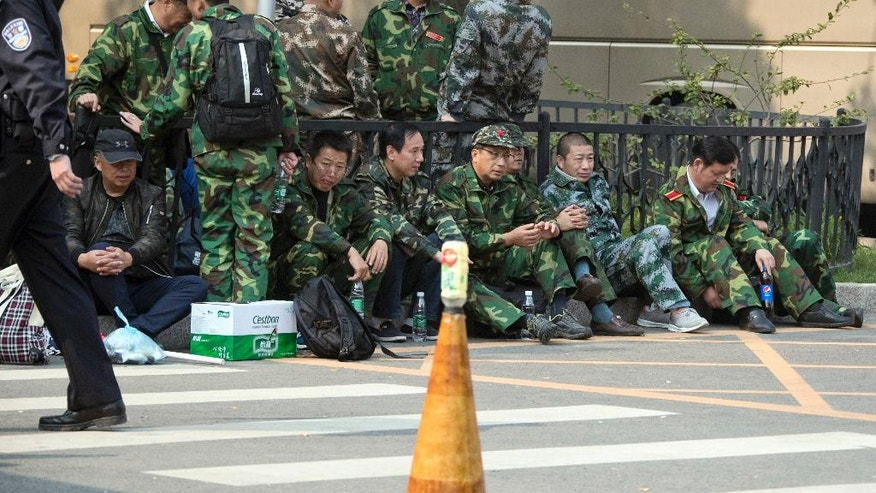 FILE - In this Tuesday, Oct. 11, 2016 file photo, protesters in green fatigues gather outside the Chinese Ministry of National Defense to protest in Beijing. Fed up with paltry pensions and benefits, China's veterans are increasingly taking to the streets, hoping to shame the government into recognizing its obligation to those who battled along the country's borders, often in extremely harsh conditions. (AP Photo/Ng Han Guan, File)