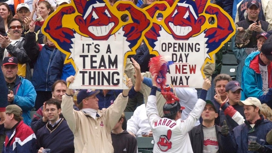 "FILE - In this April 8, 2002, file photo, fans hold up Chief Wahoo signs as they celebrate the Cleveland Indians' win over the Minnesota Twins, in Cleveland, Ohio. A Toronto court will hear arguments Monday, Oct. 17, 2016 on an attempt to bar the Cleveland Indians from using their team name and ""Chief Wahoo"" logo in Ontario.  (AP Photo/Tony Dejak, File)"
