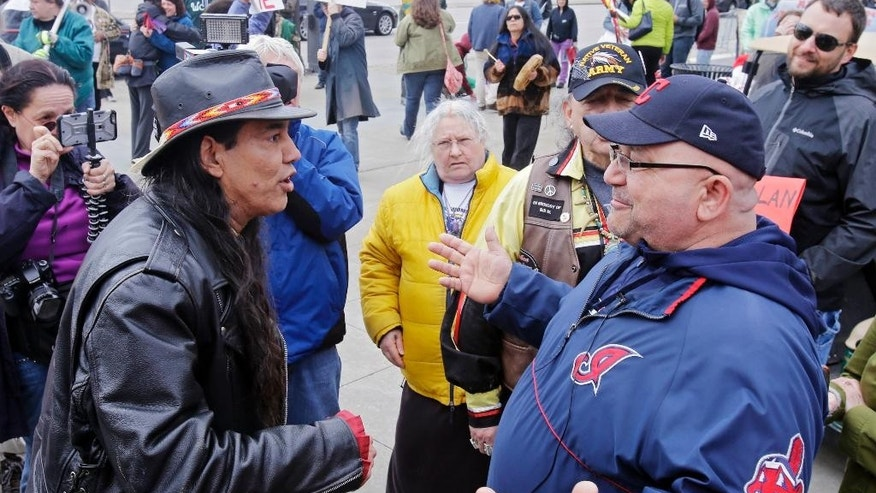 "FILE - In this April 10, 2015, file photo, Philip Yenyo, left, executive director of the American Indians Movement for Ohio, talks with a Cleveland Indians fan before a baseball game against the Detroit Tigers, in Cleveland. A Toronto court will hear arguments Monday, Oct. 17, 2016,  on an attempt to bar the Cleveland Indians from using their team name and ""Chief Wahoo"" logo in Ontario. The long-standing logo, which appears on some team caps and jerseys, depicts a grinning, red-faced cartoon with a feather headband. (AP Photo/Mark Duncan, File)"