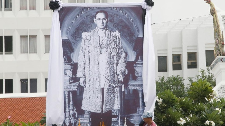 A Thai worker decorates a giant portrait of the late Thai King Bhumibol Adulyadej outside the Grand Palace in Bangkok, Thailand, Monday, Oct. 17, 2016. Tens of thousands of people are thronging at the palace complex to pay their last respects to a beloved monarch who dominated the memories of generations of Thais. (AP Photo/Sakchai Lalit)