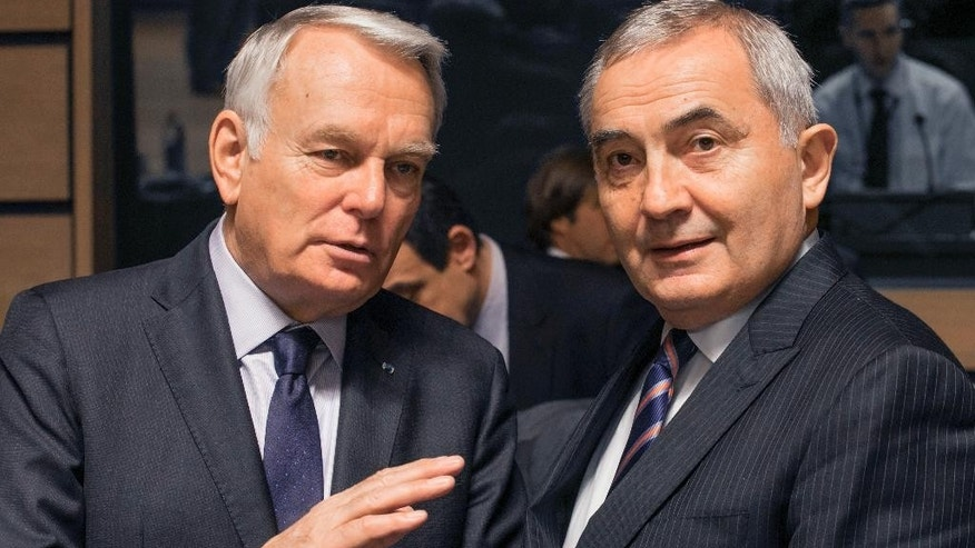 French foreign minister  Jean-Marc Ayrault, left, speaks with Romania's foreign minister Lazar Comanescu, during a meeting of EU foreign ministers at the EU Council building in Luxembourg, Monday, Oct. 17, 2016. European Union foreign ministers debated Monday whether to extend sanctions against the Syrian regime as political efforts to secure a cease-fire and access for humanitarian aid falter. (AP Photo/Olivier Matthys)