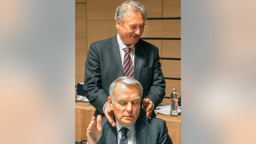Belgium's foreign minister Jean Asselborn background reacts with French foreign minister Jean-Marc Ayrault, during a meeting of EU foreign ministers at the EU Council building in Luxembourg, Monday, Oct. 17, 2016. European Union foreign ministers debated Monday whether to extend sanctions against the Syrian regime as political efforts to secure a cease-fire and access for humanitarian aid falter. (AP Photo/Olivier Matthys)