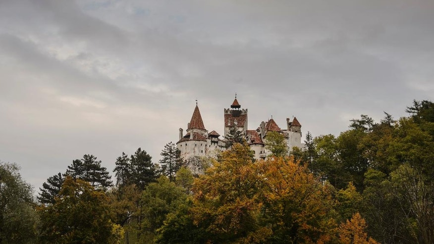 In this picture taken Oct. 9, 2016, Bran Castle lies on top of cliffs in Bran, Romania. Airbnb has launched a contest to find two people to stay overnight in the castle on Halloween, popularly known as Dracula's castle because of its connection to the cruel real-life prince Vlad the Impaler, who inspired the legend of Dracula. (AP Photo/Andreea Alexandru)