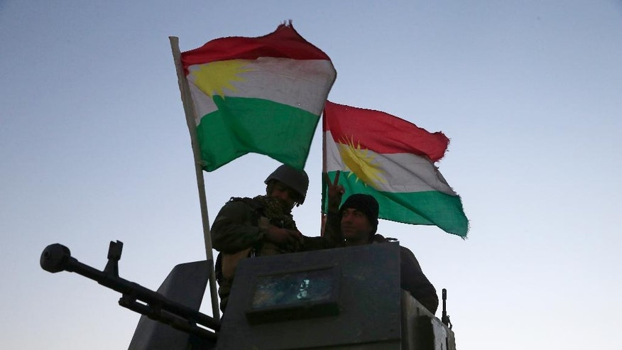 Kurdish Peshmerga fighters stand on top of a military vehicle as they advance towards villages surrounding Mosul, in Khazer, about 30 kilometers (19 miles) east of Mosul, Iraq, Monday, Oct. 17, 2016. The Iraqi military and the country's Kurdish forces say they launched operations to the south and east of militant-held Mosul early Monday morning. (AP Photo/Bram Janssen)