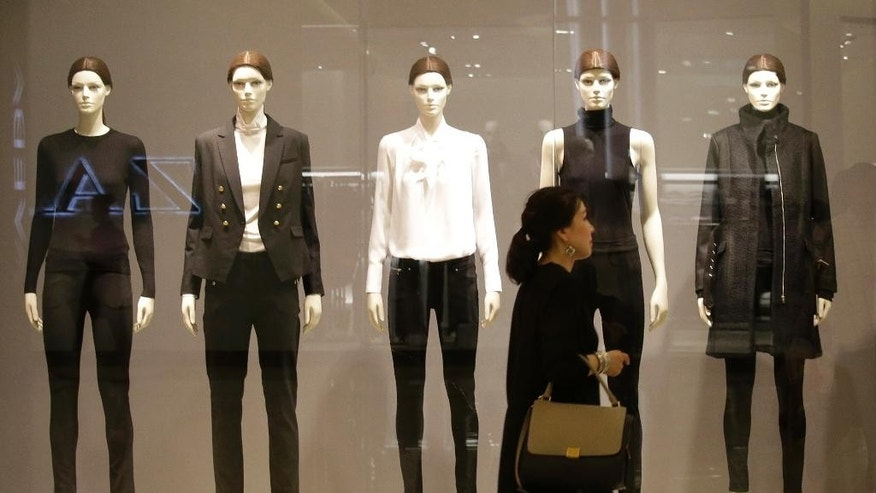A woman walks in front of a display of mannequins wearing black and white clothing at a shopping mall in Bangkok, Thailand, Monday, Oct. 17, 2016. Authorities are urging calm as social media throbs with criticism of people who aren't wearing black and white clothing to mourn the revered monarch and some arch-royalists take to reprimanding people in public. (AP Photo/Sakchai Lalit)