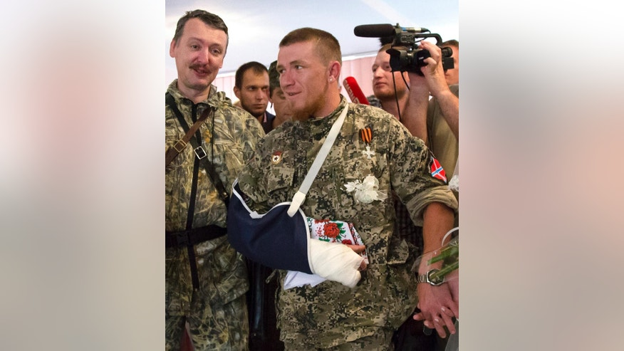 FILE - In this Friday, July 11, 2014 file photo, a platoon commander Arsen Pavlov, also known as Motorola, center, attends his and Elena Kolenkina's wedding ceremony with Igor Strelkov, left, a pro-Russian separatist commander, in Donetsk, eastern Ukraine. The separatist mouthpiece Donetsk News Agency said on Sunday, Oct. 16, 2016, Pavlov was killed in Donetsk when a bomb went off in an elevator in the house he was staying. (AP Photo/Dmitry Lovetsky, File)