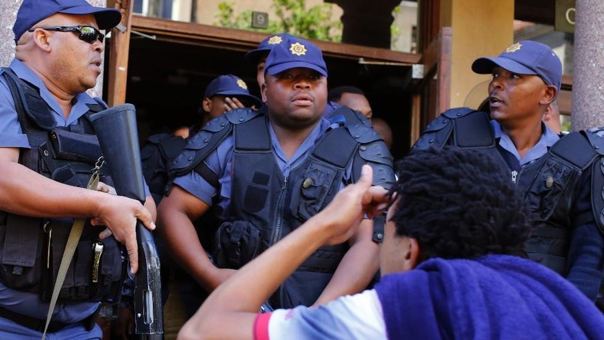 South African police disperse students after they broke a window at the University of Cape town campus in Cape Town, South Africa, Monday, Oct. 17, 2016. The University of Cape Town re-opened Monday after closing because of security concerns, but police were on campus and used a stun grenade to disperse protesters outside a university building. (AP Photo/Schalk van Zuydam)