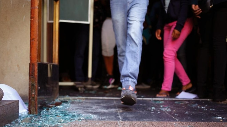 Students walk over broken glass at the entrance to a University of Cape town campus building during protest in Cape Town, South Africa, Monday, Oct. 17, 2016. The University of Cape Town re-opened Monday after closing because of security concerns, but police were on campus and used a stun grenade to disperse protesters outside a university building. (AP Photo/Schalk van Zuydam)