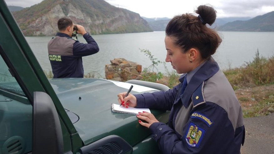 In this picture taken on Oct. 11, 2016, a border guard looks through binoculars on the Danube in the area of Calafat, Romania. Romania has invested in border control to prevent migrants illegally passing through the country on their way to Western Europe, and the efforts seem to be working. Migrants have proved ingenious in their sometimes life-threatening attempts to illegally enter Romania. They hide under trucks, take the short but perilous journey across the Danube or simply walk under cover of darkness from Serbia into Romania. (AP Photo/Olimpiu Gheorghiu)