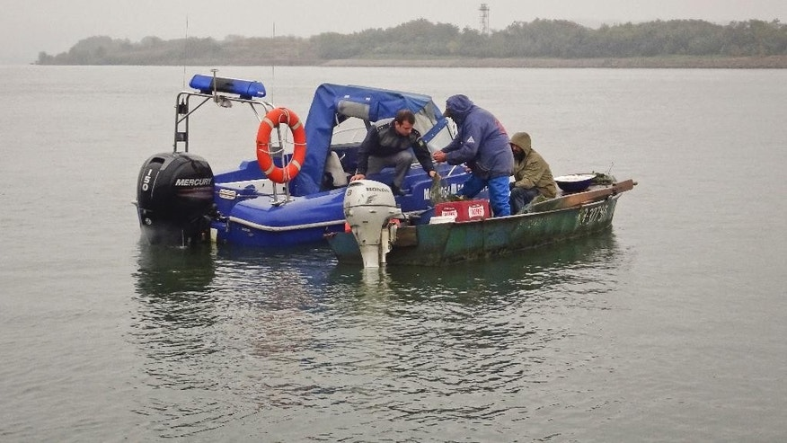 In this photo taken on Oct. 11, 2016, border guards board a fishing boat for checks on the Danube in the area of Calafat, Romania. Romania has invested in border control to prevent migrants illegally passing through the country on their way to Western Europe, and the efforts seem to be working. Migrants have proved ingenious in their sometimes life-threatening attempts to illegally enter Romania. They hide under trucks, take the short but perilous journey across the Danube or simply walk under cover of darkness from Serbia into Romania. (AP Photo/Olimpiu Gheorghiu)