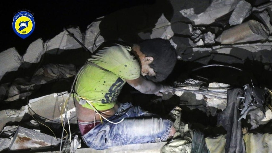 In this photo released early Monday, Oct. 17, 2016 and provided by the Syrian Civil Defense group known as the White Helmets, rescue workers trying to remove a boy stuck in the debris of a building in the neighborhood of Qaterji in rebel-held east Aleppo following an airstrike in Aleppo, Syria. Syrian activists are reporting that airstrikes on a rebel-held, eastern neighborhood in the city of Aleppo have killed at least 13 people, including children. The Britain-based Syrian Observatory for Human Rights says the airstrikes hit the Marjeh neighborhood. (Syrian Civil Defense White Helmets via AP)
