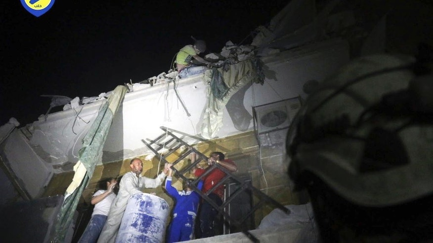 In this photo released early Monday, Oct. 17, 2016 and provided by the Syrian Civil Defense group known as the White Helmets, rescue workers try to remove a boy stuck in the debris of a building in the neighborhood of Qaterji in rebel-held east Aleppo following an airstrike in Aleppo, Syria. Syrian activists are reporting that airstrikes on a rebel-held, eastern neighborhood in the city of Aleppo have killed at least 13 people, including children. The Britain-based Syrian Observatory for Human Rights says the airstrikes hit the Marjeh neighborhood. (Syrian Civil Defense White Helmets via AP)