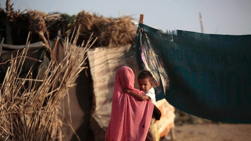 In this photo taken on Thursday, Oct. 6, 2016, a displaced girl holds her brother at a camp for internally displaced people near the town of Abs, located on Yemen's western coastal plain below towering desert mountains. Hundreds of Yemenis fleeing war are now living in tents and mud-brick shelters scattered across a cornfield, where they buried the remains of loved ones they carried with them when they escaped. (AP Photos Hani Mohammed)