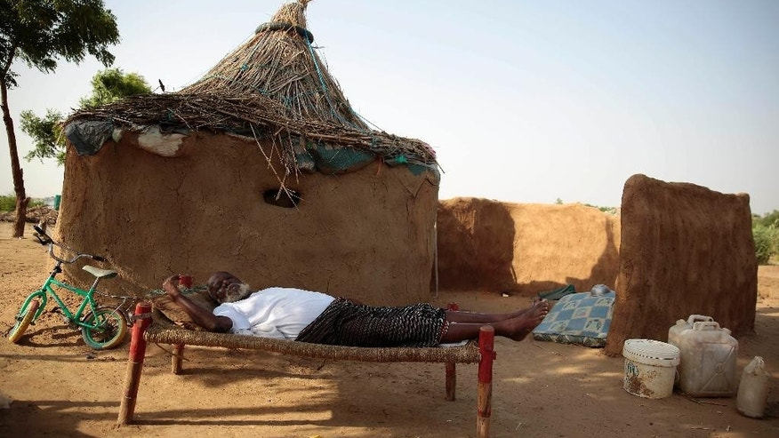 In this photo taken on Friday, Oct. 7, 2016, an elderly man lies on a bed in front of his hut at a camp for internally displaced people near the town of Abs, located on Yemen's western coastal plain below towering desert mountains. Hundreds of Yemenis fleeing war are now living in tents and mud-brick shelters scattered across a cornfield, where they buried the remains of loved ones they carried with them when they escaped. (AP Photos Hani Mohammed)