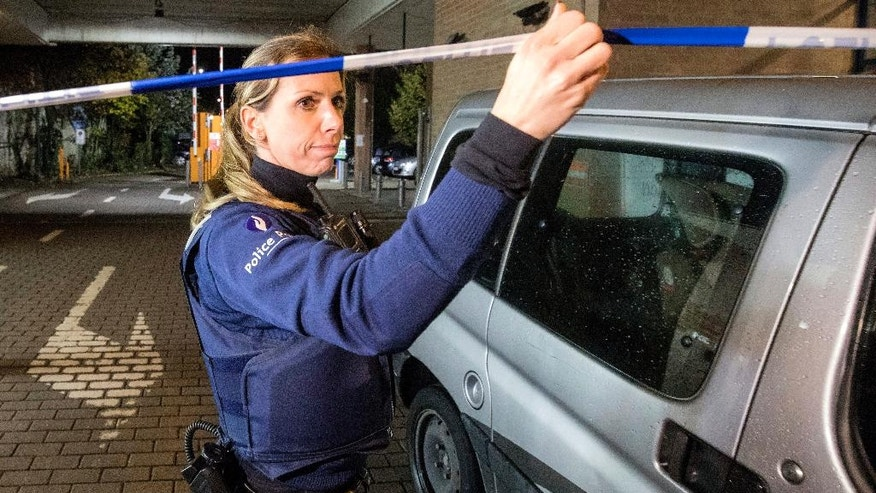 A police officer secures the area near a Carrefour supermarket in Brussels, Tuesday, Oct. 18, 2016, after a man held a group of people hostage in the supermarket. Authorities say they saw no immediate terror motive which ended without injuries.  (AP Photo/Olivier Matthys)