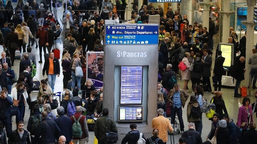 Travelers walk through St Pancras International train station in London, as Eurotunnel trains were suspended on Tuesday, Oct. 18, 2016. An electrical supply problem in the train tunnel beneath the English Channel has blocked Eurostar traffic between Britain and the European continent. (AP Photo/Frank Augstein)