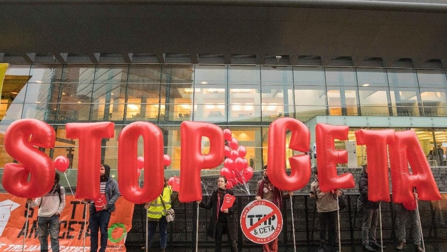 Protestors hold inflatable letters as they demonstrate outside a meeting venue of EU trade ministers at the EU Council building in Luxembourg, Tuesday, Oct. 18, 2016. European Union trade ministers meet Tuesday to discuss the Comprehensive Economic and Trade Agreement between the EU and Canada. (AP Photo/Olivier Matthys)