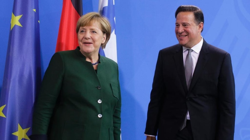 German Chancellor Angela Merkel, left, and Panama's President Juan Carlos Varela leave a news conference after talks at the chancellery in Berlin, Tuesday, Oct. 18, 2016. (AP Photo/Markus Schreiber)