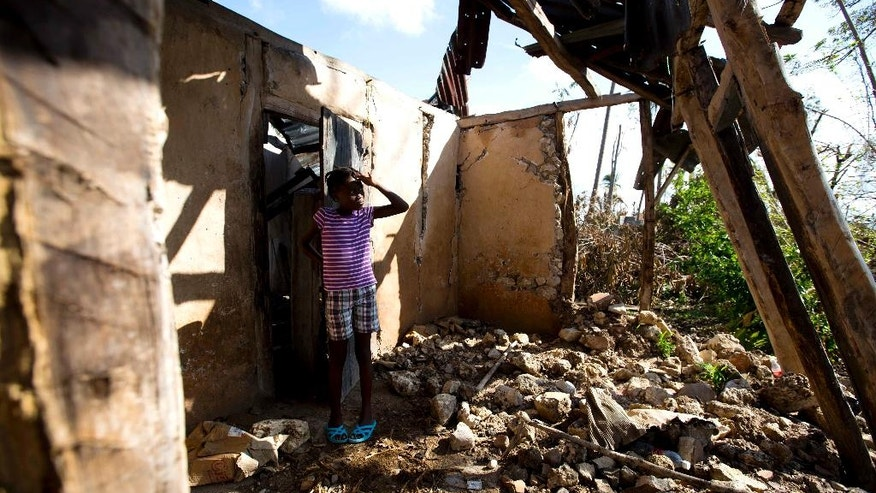 Love Manie Simeus, 12, stands in what's left of her grandmother's home after Hurricane Matthew hit her village Mersan, located in Camp-Perrin, a district of Les Cayes, Haiti, Monday, Oct. 17, 2016. It's been two weeks since the Category 4 hurricane hit Haiti, killing hundreds of people and destroying tens of thousands of flimsy homes. School has been interrupted for more than 100,000 children. (AP Photo/Dieu Nalio Chery)