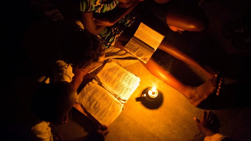 Love Manie Simeus, 12, reads the Bible by candlelight in her school's classroom where she and other residents have taken refuge after Hurricane Matthew destroyed their homes, in the village of Mersan, located in Camp-Perrin, a district of Les Cayes, Haiti, Sunday, Oct. 16, 2016. While her school is used as a shelter, Love has been trying to keep her mind sharp by reading the Bible to illiterate storm refugees and looking through school library books that made it through the storm. (AP Photo/Dieu Nalio Chery)