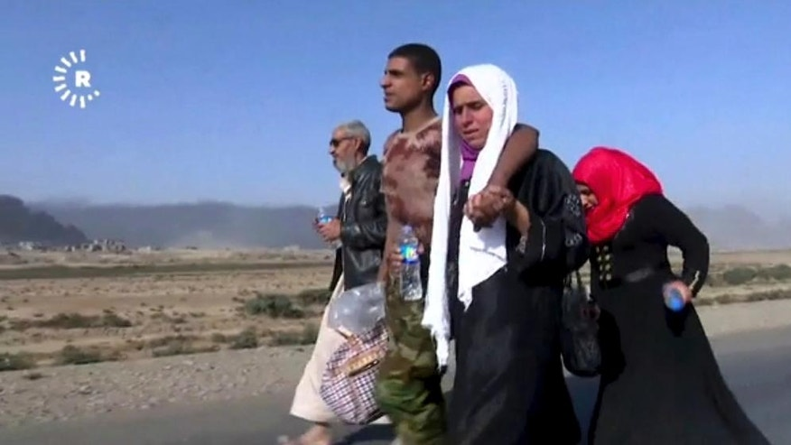 This image made from video by Rudaw News Agency shows a family fleeing Mosul, Iraq on Tuesday, Oct. 18, 2016. Residents who have endured more than two years of militant rule describe a city under siege, and say a new sense of terror has set in since Iraq announced the start of a long awaited operation to liberate its second largest city. (Rudaw News Agency via AP)