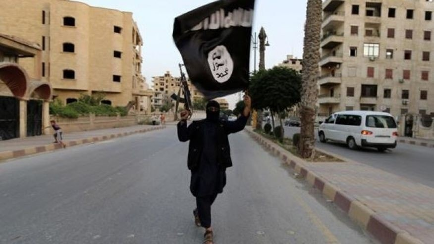 June 29, 2014: A member loyal to the Islamic State in Iraq and the Levant (ISIS) waves an ISIS flag in Raqqa, Iraq.