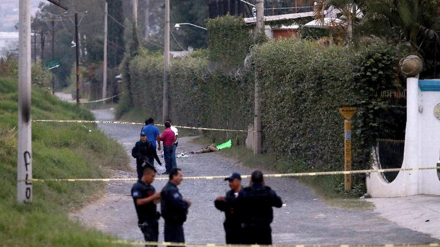 Police secure the area where six people were found alive with their hands cut off, along with another person who was killed, in the background, in Tlaquepaque on the outskirts of Guadalajara, Mexico, Tuesday, Oct. 18, 2016. Investigators believe the mutilations and the killing were revenge for an unpaid drug payment involving members of the same cell of a criminal group. (AP Photo/Fernando Carranza)