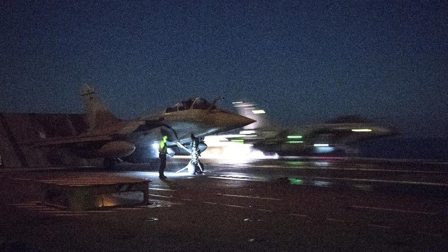 This photo taken on Sunday, Oct. 16, 2016 and released on Tuesday, Oct. 18, 2016 by the French Army Communications Audiovisual office (ECPAD) shows French army Rafale fighter jets taking off from the deck of France's aircraft carrier Charles De Gaulle, in the Mediterranean sea. Seven French Rafale jets, from the Air Force and the Navy, carried out airstrikes south of Mosul overnight Oct. 15-16 with SCALP missiles that destroyed a factory making IEDs (improvised explosive devices). (ECPAD via AP)