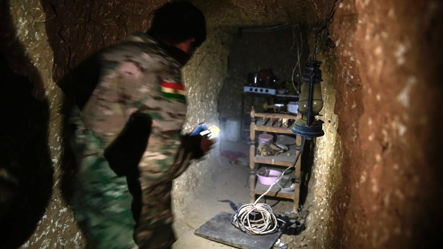 A peshmerga fighter walks through the kitchen of an underground tunnel made by Islamic State fighters, Tuesday, Oct. 18, 2016. The Kurdish forces found the tunnel in the town of Badana that was liberated from the Islamic State group on Monday. The fighters built tunnels under residential areas so they could move without being seen from above to avoid airstrikes. (AP Photo/Bram Janssen)