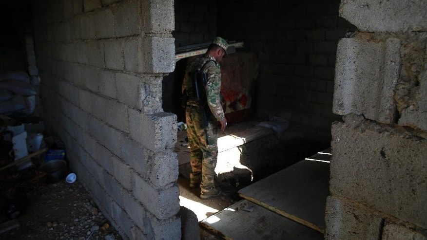 A peshmerga fighter looks into an underground tunnel built by Islamic State fighters, Tuesday, Oct. 18, 2016. The Kurdish forces found the tunnel in the town of Badana that was liberated from the Islamic State group one day earlier. The fighters built tunnels under residential areas so they could move without being seen from above to avoid airstrikes. (AP Photo/Bram Janssen)
