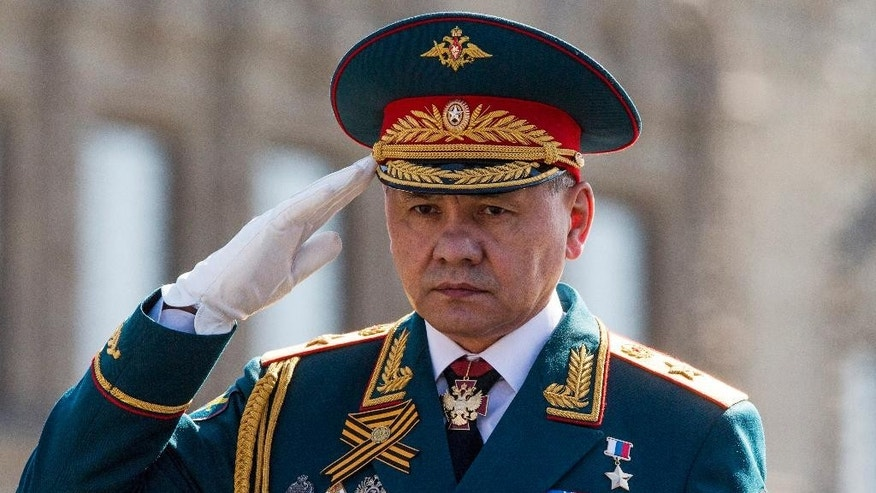 FILE - In this Saturday, May 7, 2016 file photo, Russian Defense Minister Sergei Shoigu salutes to his soldiers as he is driven along Red Square during a rehearsal for the Victory Day military parade which will take place at Moscow's Red Square on May 9 to celebrate 71 years after the victory in WWII in Moscow, Russia. Shoigu says the airstrikes were suspended starting from 10 a.m. on Tuesday, Oct. 18 and the suspension is intended to prepare for the opening of humanitarian corridors for the rebels to leave the besieged city of Aleppo. (AP Photo/Alexander Zemlianichenko, file)
