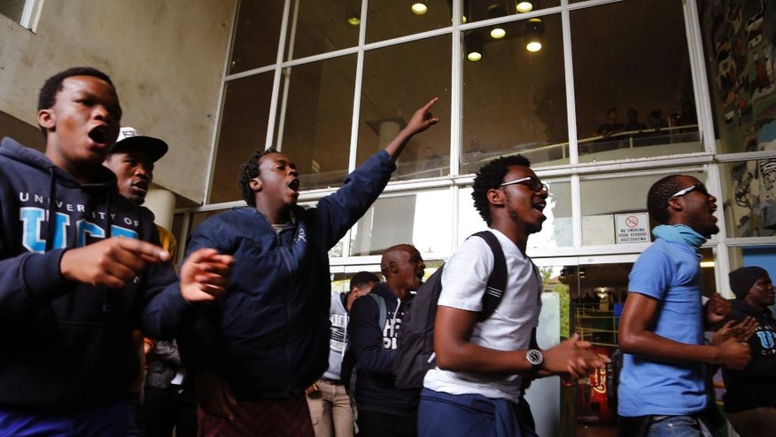 Students from the University of Cape Town protest for free education by disrupting classes in Cape Town, South Africa, Tuesday, Oct. 18, 2016. The University of Cape Town re-opened Monday after closing because of security concerns, but police were on campus and used a stun grenade to disperse protesters outside a university building. Another building was evacuated because of vandalism by protesters who tossed sewage in the corridors, said the statement. (AP Photo/Schalk van Zuydam)