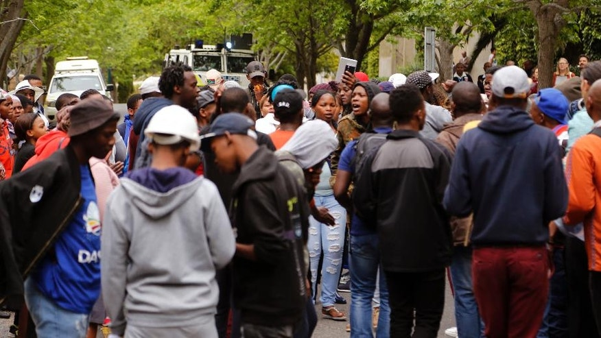 Students from the University of Cape Town gather as they take part in a protest for free education by disrupting classes in Cape Town, South Africa, Tuesday, Oct. 18, 2016. The University of Cape Town re-opened Monday after closing because of security concerns, but police were on campus and used a stun grenade to disperse protesters outside a university building. Another building was evacuated because of vandalism by protesters who tossed sewage in the corridors, said the statement. (AP Photo/Schalk van Zuydam)