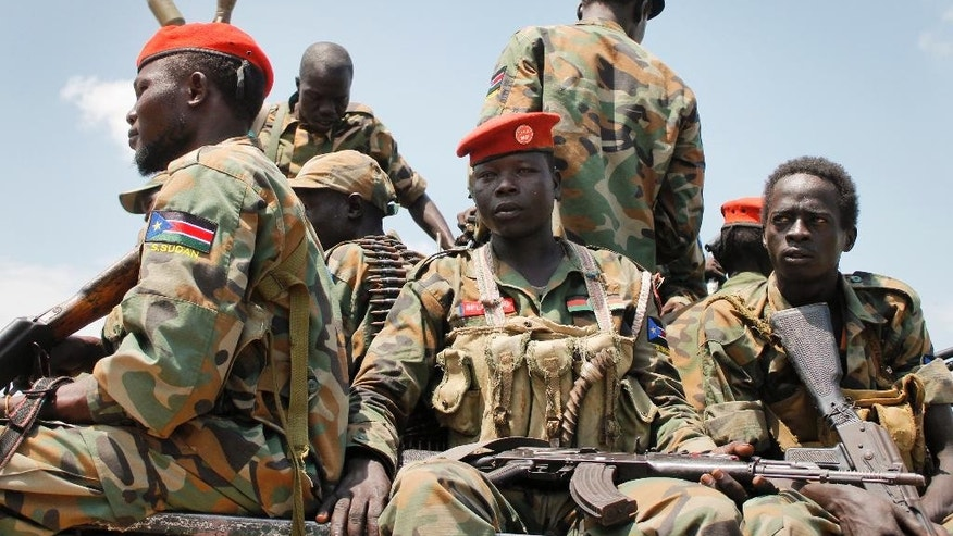 In this photo taken Sunday, Oct. 16, 2016, a group of South Sudanese government soldiers sit on the back of a pickup truck before visiting the scene of a recent battle in Malakal, South Sudan. Following clashes last week in the outskirts of the city, which has been reduced to rubble and almost entirely deserted by civilians, the army flew in journalists on Sunday to show that they retain control of the strategic city, even though rebels still vow to take it. (AP Photo/Justin Lynch)