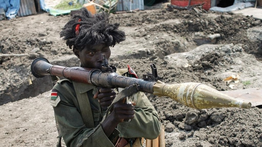 In this photo taken Sunday, Oct. 16, 2016, a South Sudanese government soldier wearing a wig holds a rocket propelled grenade launcher while standing in a trench in Malakal, South Sudan. Following clashes last week in the outskirts of the city, which has been reduced to rubble and almost entirely deserted by civilians, the army flew in journalists on Sunday to show that they retain control of the strategic city, even though rebels still vow to take it. (AP Photo/Justin Lynch)