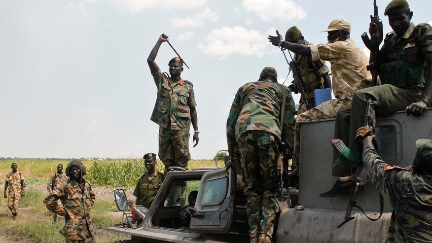 In this photo taken Sunday, Oct. 16, 2016, South Sudanese army spokesperson Lul Ruai Koang, center left, stands on a vehicle near the site of a recent battle, in Malakal, South Sudan. Following clashes last week in the outskirts of the city, which has been reduced to rubble and almost entirely deserted by civilians, the army flew in journalists on Sunday to show that they retain control of the strategic city, even though rebels still vow to take it. (AP Photo/Justin Lynch)