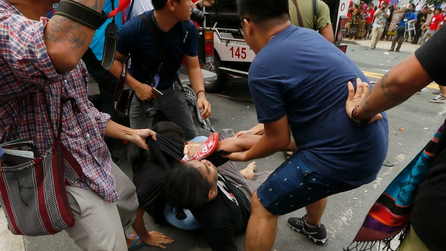 Oct. 19, 2016: A protester is helped after a Philippine National Police van, background, rammed into protesters outside the U.S. Embassy in Manila, Philippines injuring an undetermined number.