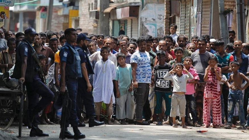 FILE - In this Aug. 27, 2016 file photo, Bangladeshis gather near a site of a shoot-out in Narayanganj, on the outskirts of Dhaka, where police said they killed three suspected militants, including Tamim Chowdhury, a Bangladeshi-born Canadian, who police believe was one of two masterminds of the attack on a popular restaurant in Dhaka. In the three months since a band of youths tortured and killed 20 hostages in the Dhaka restaurant, intelligence officials say they're rooting out radicals and restoring security to the streets. Police raids that have killed about 40 suspected Islamist militants; hundreds of suspects detained in police dragnets; and new information on how the attack was financed by local sympathizers. (AP Photo/File)