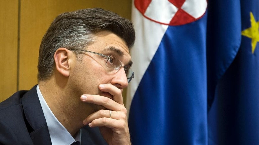 New Croatian Prime Minister, Andrej Plenkovic, listens during a parliament session in Zagreb, Croatia, Wednesday, Oct. 19, 2016. Lawmakers in Croatia approved a new government on Wednesday as the prime minister promised to boost economic recovery and overcome political divisions in the European Union's newest member state.(AP Photo/Darko Bandic)