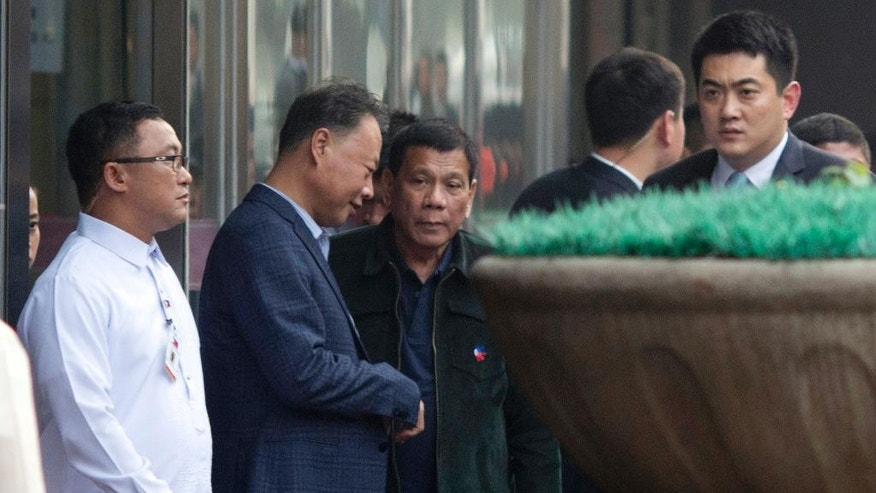 Philippine President Rodrigo Duterte, center walks out from a shopping mall in Beijing, China, Wednesday, Oct. 19, 2016. This week's visit to China by Duterte points toward a restoration of trust between the sides following recent tensions over their South China Sea territorial dispute, China's official news agency said Tuesday. (AP Photo/Ng Han Guan)