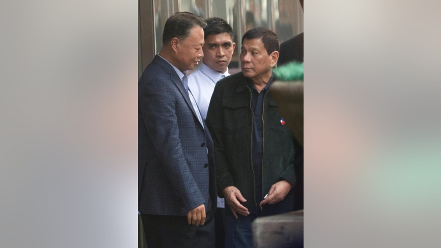 Philippine President Rodrigo Duterte, right, prepares to leave from a shopping mall in Beijing, China, Wednesday, Oct. 19, 2016. This week's visit to China by Duterte points toward a restoration of trust between the sides following recent tensions over their South China Sea territorial dispute, China's official news agency said Tuesday. (AP Photo/Ng Han Guan)