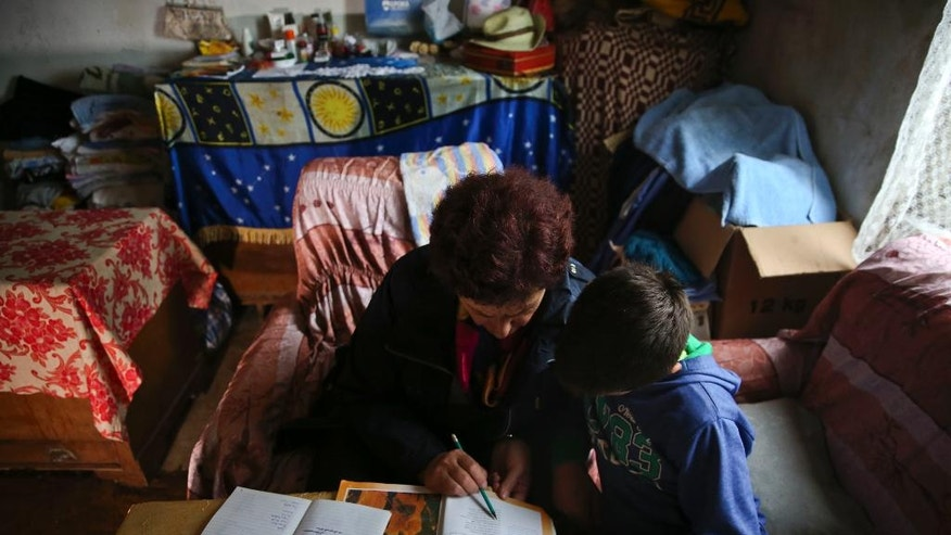 In this Friday, Oct. 7, 2016 photo, Albanian teacher Liljana Luani teaches her student who asked not be identified, isolated in the family house fearing a blood feud vendetta in northern Albania. Where most people and even police fear to set foot, Liljana Luani takes books, household supplies, and a lifetime of experience on how to help families marked for murder. The 56-year-old school teacher from Shkodra in northern Albania uses her spare time to travel to remote hillside villages where children are trapped in a centuries-old tradition of blood feuds and hidden by their families. (AP Photo/Visar Kryeziu)
