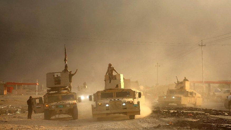 An Iraqi military convoy advances towards the city of Mosul, Iraq, Wednesday, Oct. 19, 2016. A senior Iraqi general on Wednesday called on Iraqis fighting for the Islamic State group in Mosul to surrender as a wide-scale operation to retake the militant-held city entered its third day. (AP Photo)