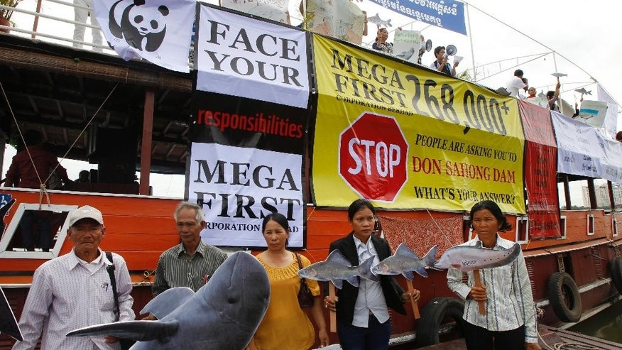 FILE - In this Sept. 11, 2014 file photo, Cambodian non-governmental organization (NGOs) activists hold a cut-out of Mekong dolphin, left, and cut-out of other species during a protest against a proposed Don Sahong dam, in Phnom Penh, Cambodia. Consultations for the contentious Xayaburi and Don Sahong dams by Laos on the Mekong's mainstream severely damaged the Mekong River Commission's credibility. Cambodia, Vietnam and Thailand opposed the Lao plans, fearing damage to fisheries and the Mekong's rice bowl delta, and the commission failed to broker an agreement. (AP Photo/Heng Sinith)