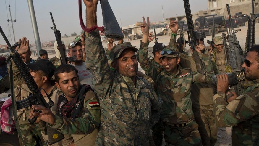 Iraqi army soldiers raise their weapons in celebration on the outskirts of Qayyarah, Iraq, Wednesday, Oct. 19, 2016. A senior Iraqi general on Wednesday called on Iraqis fighting for the Islamic State group in Mosul to surrender as a wide-scale operation to retake the militant-held city entered its third day. (AP Photo/Marko Drobnjakovic)