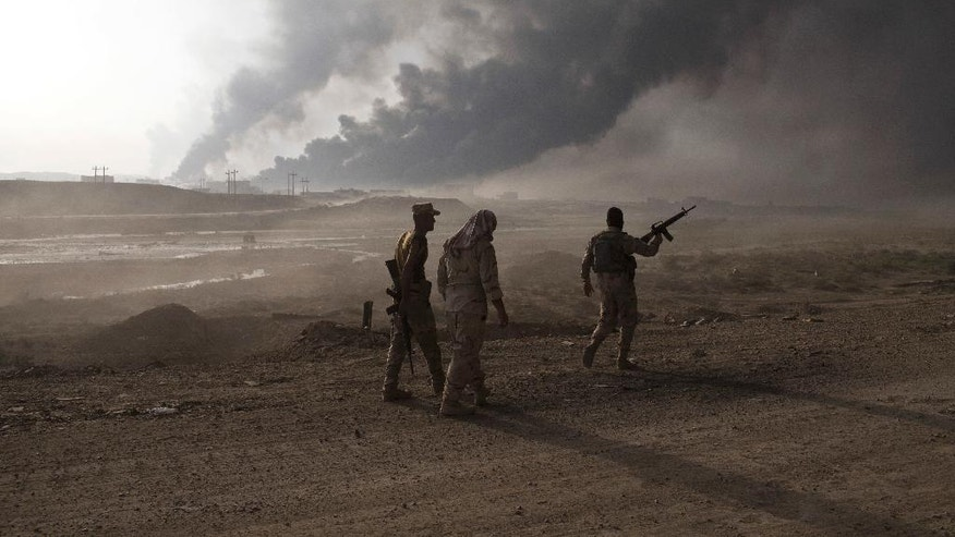 Iraqi army soldiers man a checkpoint as oil wells burn on the outskirts of Qayyarah, Iraq, Wednesday, Oct. 19, 2016. A senior Iraqi general on Wednesday called on Iraqis fighting for the Islamic State group in Mosul to surrender as a wide-scale operation to retake the militant-held city entered its third day. (AP Photo/Marko Drobnjakovic)
