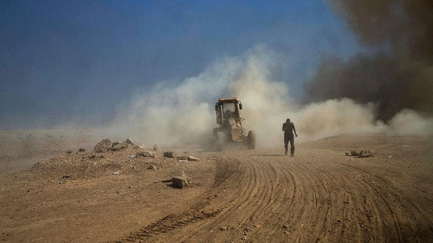 An Iraqi army contractor gets out of a road construction vehicle after being hit by an improvised explosive device on the outskirts of Qayyarah, Iraq, Wednesday, Oct. 19, 2016. A senior Iraqi general on Wednesday called on Iraqis fighting for the Islamic State group in Mosul to surrender as a wide-scale operation to retake the militant-held city entered its third day. (AP Photo/Marko Drobnjakovic)
